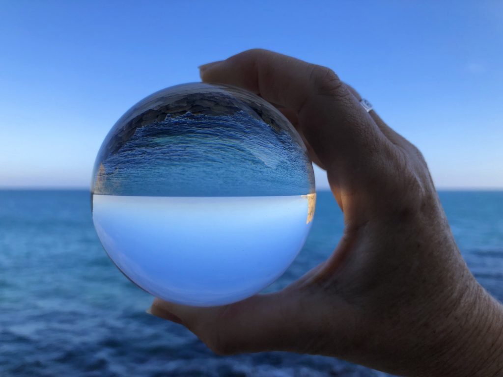 Crystal ball held in a woman's hand, looking to the sea, horizon and clear blue sky