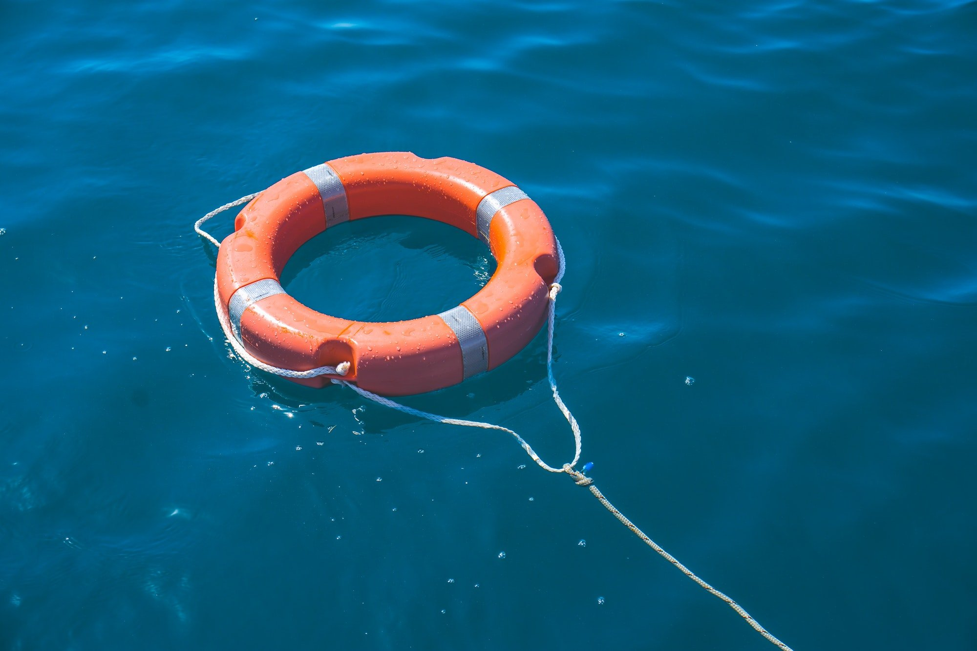 *Nominated* Orange rescue buoy floating on colorful water